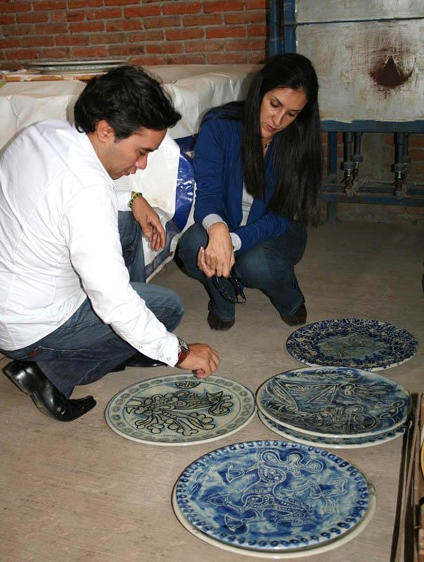 Carlos and Claudia Luna examining ceramics before an exhibition, Puebla, Mexico, 2010