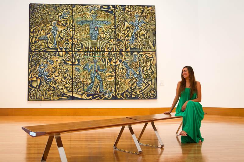 "Camila Luna sitting with ""El Gran Mambo."" Green Machine: The Art of Carlos Luna; Frost Art Museum, Miami, FL"